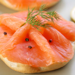 Smoked salmon on bagel with fresh black pepper.