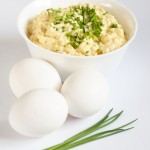 White bowl with egg spread, eggs, and chive
