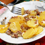 fork in dish with baked potato slices and minced meat