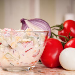 Fresh salad with tomato, cucumber, onion and eggs dressed with sour cream