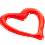 heart shaped red strawberry syrup on white background