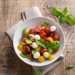 Italian Caprese salad with cherry tomatoes and mini mozzarella, selective focus