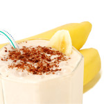 milky banana cocktail with a slice of banana and grated chocolate with bananas